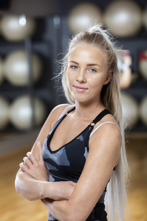waistup: Portrait of confident young woman standing arms crossed in gym