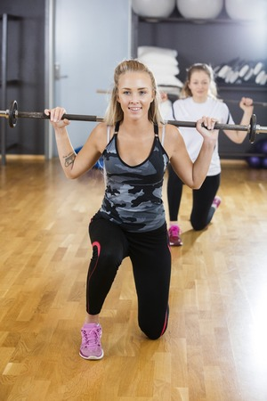 woman kneeling: Smiling young woman kneeling while lifting barbell in gym