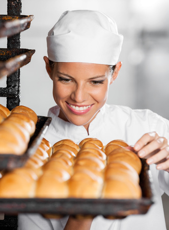 bakery: Beautiful female baker looking at freshly baked breads in bakery