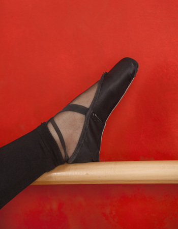 shoes woman: Closeup of young ballerinas leg on barre against red wall Stock Photo