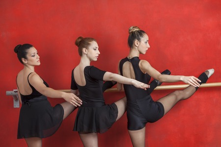 barre: Rear view of young ballerinas performing at barre against red wall in studio Stock Photo