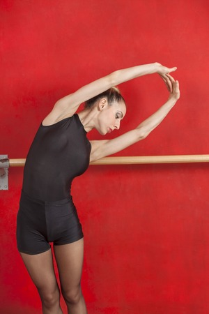 barre: Young ballerina stretching with arms raised against red wall in ballet studio Stock Photo