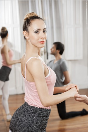 Portrait of confident dancer holding ballet trainers hand while practicing in studio
