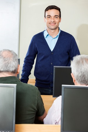tutor: Portrait of smiling tutor standing in computer class while senior male students sitting at desk