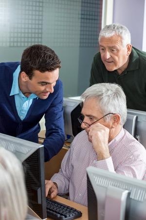 the elderly tutor: Young male teacher explaining senior men in computer class Stock Photo