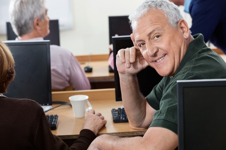 the elderly tutor: Side view portrait of happy senior man sitting at desk in computer class