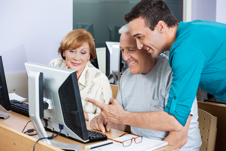 the elderly tutor: Young male tutor assisting senior students in using computer at class Stock Photo