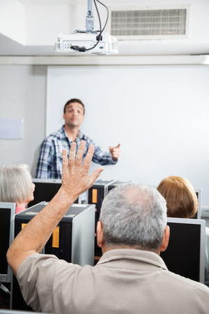 the elderly tutor: Senior male student raising hand while tutor explaining in computer class