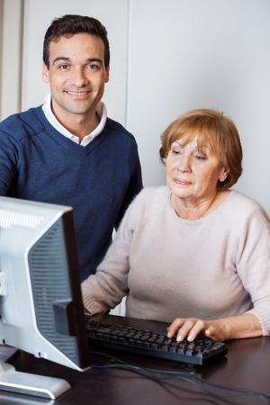 the elderly tutor: Portrait of happy tutor assisting senior woman in using computer at desk