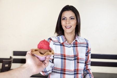 gelati: Mid adult woman receiving ice cream from waiter in parlor