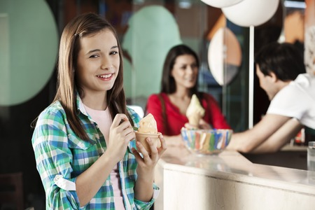gelati: Portrait of happy girl having ice cream while mother and waiter standing at counter in parlor Stock Photo