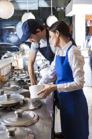 mid adult male: Mid adult male and female workers preparing ice creams at counter in parlor