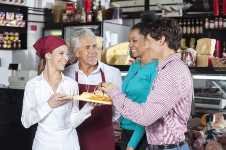 salespeople: Happy salespeople offering free samples to customers in cheese shop Stock Photo