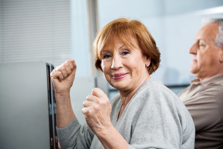 senior woman: Portrait of happy senior woman cheering with classmate in background at computer class Stock Photo