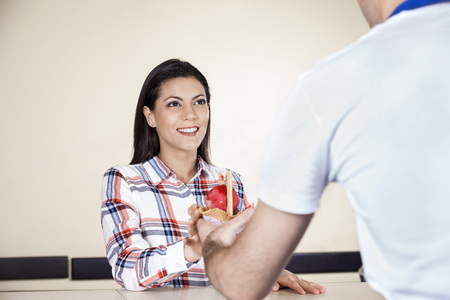 woman ice cream: Smiling woman receiving ice cream from waiter in parlor