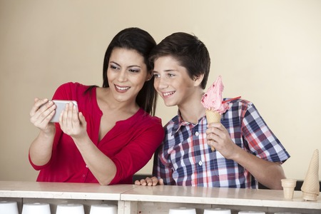 tomando refresco: Feliz mujer de mediana edad teniendo autorretrato con el hijo que sostiene el helado de fresa en el salón de