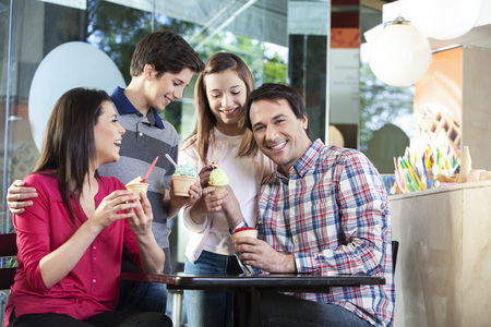 gelati: Portrait of happy mid adult man having ice cream with family in parlor Stock Photo