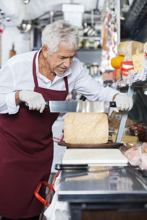 handled: Salesman slicing cheese with double handled knife at counter in shop