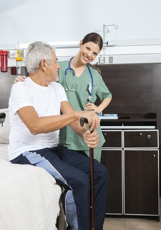 long term care services: Portrait of happy female nurse standing by senior patient sitting on bed in rehab center