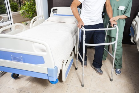 help section: Low section of female nurse helping senior male patient in using walker at rehab center