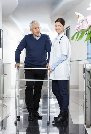 long term care services: Portrait of smiling doctor standing with senior man using walker in rehab center Stock Photo