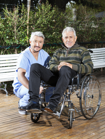 rehab: Portrait of male physiotherapist crouching by senior man in wheelchair at rehab center lawn