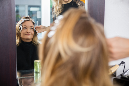 hairtician: Mature woman having her hair dyed by hairdresser at beauty parlor