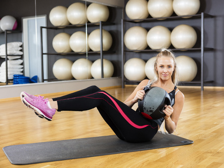 Full length portrait of confident young woman exercising with medicine ball in gym