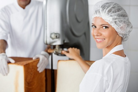 food industry: Portrait of confident female baker using cutting machine in bakery