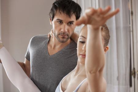 ballet clásico: Apuesto ballet del adulto mediados de la enseñanza entrenador de bailarina en el estudio Foto de archivo