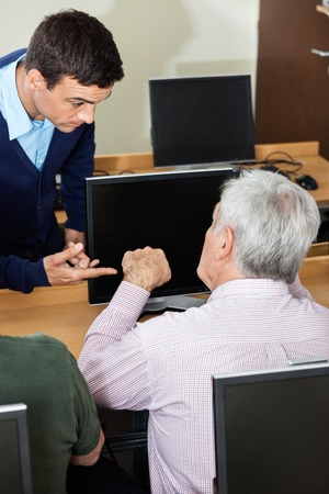 the elderly tutor: High angle view of male tutor discussing with senior man at desk in computer class