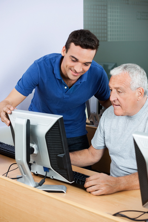 the elderly tutor: Happy male teacher assisting senior man in using computer at classroom Stock Photo
