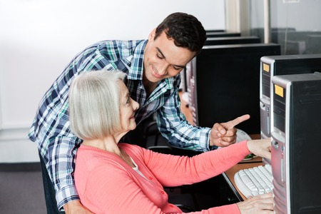 the elderly tutor: Male teacher assisting senior woman in using computer at classroom