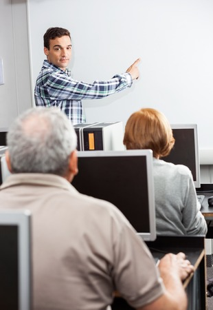 the elderly tutor: Young male teacher pointing at whiteboard while looking at senior students in computer class