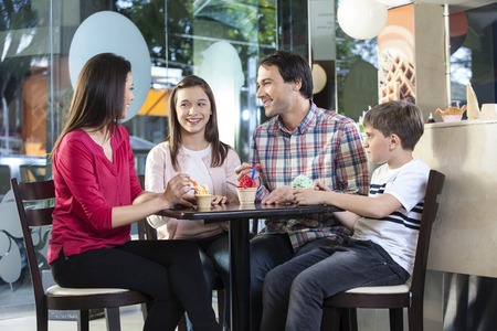 gelati: Happy family in casuals having ice creams while sitting at table in parlor
