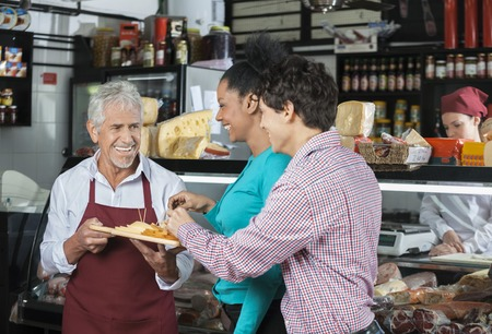 associates: Happy male salesperson offering free samples to customers in cheese shop Stock Photo