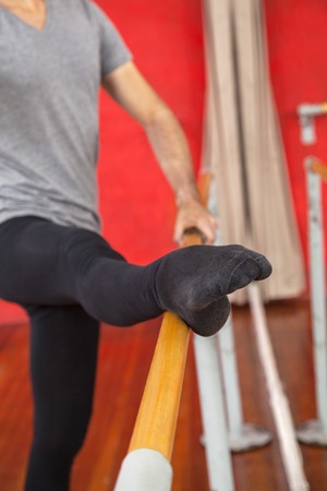 barre: Cropped image of male trainer with leg on barre at studio