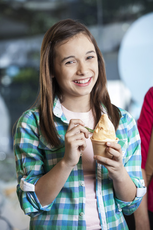 child ice cream: Portrait of happy girl holding ice cream in cup at parlor