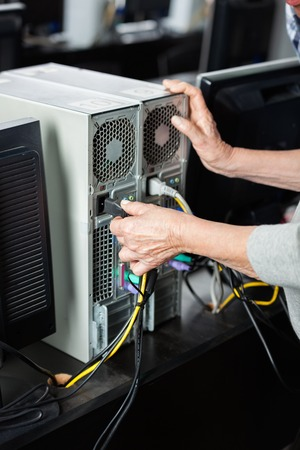 plugging: Cropped image of senior woman plugging computer in classroom