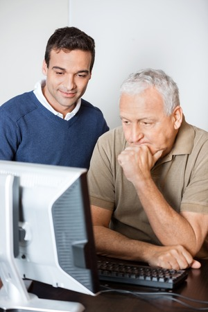 the elderly tutor: Young male teacher assisting senior student in computer class