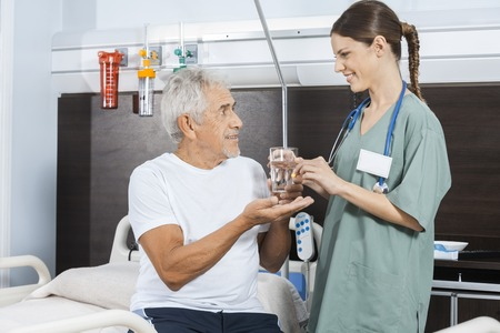 receiving: Smiling male patient receiving water glass and pill from female nurse in rehab center