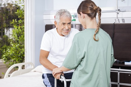long term care services: Happy senior man being assisted by female nurse in using walker at rehab center