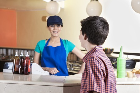 parlor: Happy waitress looking at preteen male customer at counter in ice cream parlor