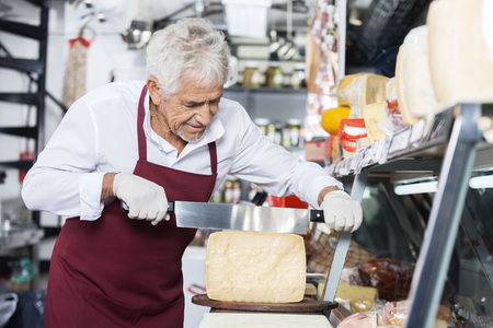 handled: Senior man wearing apron while slicing cheese with double handled knife at counter in shop