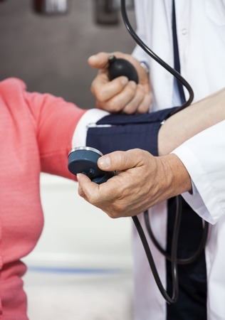 rehab: Cropped image of mature male doctor checking blood pressure of senior woman in rehab center Stock Photo