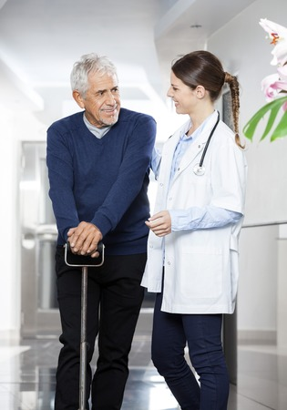 eldercare: Smiling senior patient using cane while looking at female doctor in rehab center Stock Photo