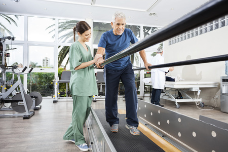 Female physiotherapist standing by smiling senior patient walking between parallel bars in rehab center