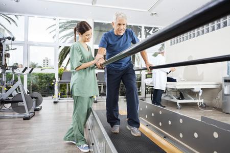 Vrouwelijke fysiotherapeut die zich door lachende senior patiënt lopen tussen parallelle staven in revalidatiecentrum Stockfoto