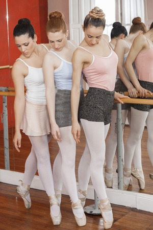 pointe: Full length of ballet dancers performing pointe on hardwood floor