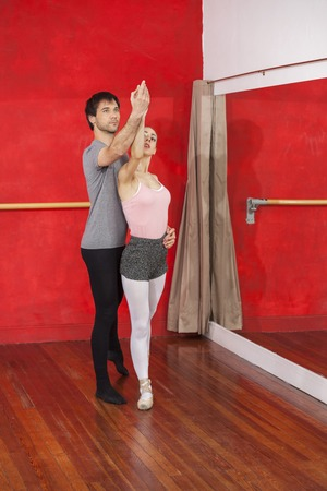 male ballet dancer: Full length of male trainer assisting female ballet dancer at studio